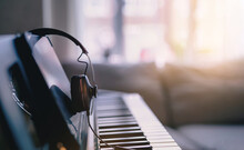 Soft Focus Digital Piano Keyboard With Headphones For Music With Blurry Of Sofa Background, Cosy Cinematic Scene Of Relaxing In Living Room With Morning Light Shining Through Window