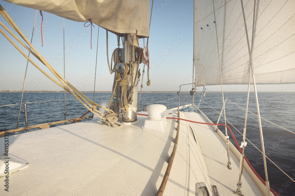 Fototapeta White sloop rigged yacht sailing in an open sea at sunset. Clear sky. A view from the deck to the bow, mast, sails. Transportation, travel, cruise, sport, recreation, leisure activity, racing, regatta - obraz na płótnie