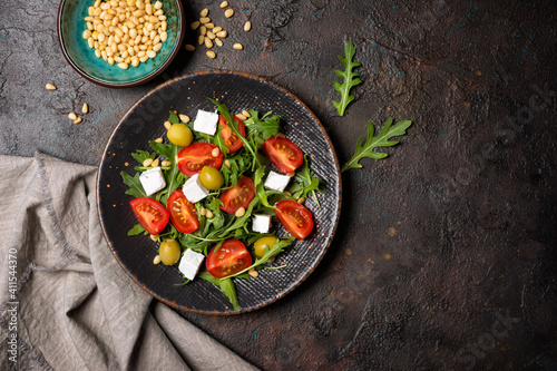 Obraz Healthy vegetarian salad with fresh arugula, cherry tomatoes, soft cheese, olives and pine nuts - fototapety do salonu