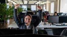 Business Woman Rejoices At Work Success. The Female Call Center Operator Raised Her Hands In Happiness At Her Desk