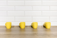 Yellow Cups On Wood Background In A Row