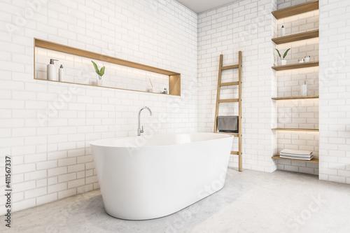 Fototapeta White bathtub and brick wall, shelves with gels and plants, marble floor obraz
