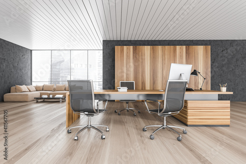 Wooden and black office room with armchairs and table with computer