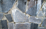 Large granite stones embedded in the wall. Stock photo with coated solid surface.