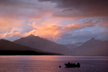 A Passing Storm At Sunset Over Lake McDonald In Glacier National Park In Montana. There Is A Boat In The Foreground And The Sky Is Light A Bright Pink And Orange From The Sunset