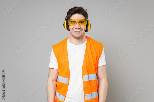 Young employee smiling happy handyman man in orange vest protective ear muffs looking camera isolated on grey background studio portrait Instruments for renovation apartment room Wallpaper Mural
