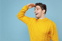 Young Smiling Optimistic Hapy Student Man 20s Wear Casual Knitted Cozy Fashionable Yellow Sweater Holding Hand At Forehead Looking Far Away Distance Isolated On Blue Color Background Studio Portrait.