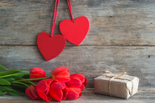Valentine Card. Bunch Of Red Tulips, Handmade Gift Box And Two Red Hearts On Old Non Paint Wooden Planks