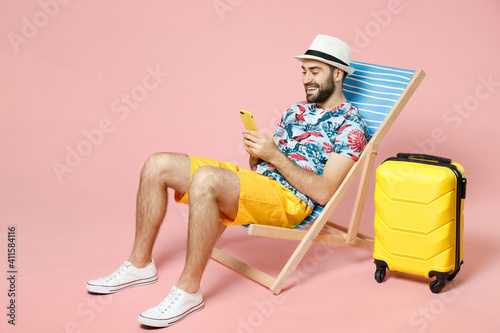 Fototapeta Full length smiling young traveler tourist man in hat sit on deck chair using mobile cell phone typing sms message isolated on pink background. Passenger travel on weekend. Air flight journey concept. obraz na płótnie