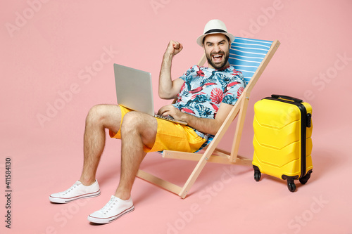 Fotografering Full length happy young traveler tourist man in hat sit on deck chair work on laptop computer doing winner gesture isolated on pink background