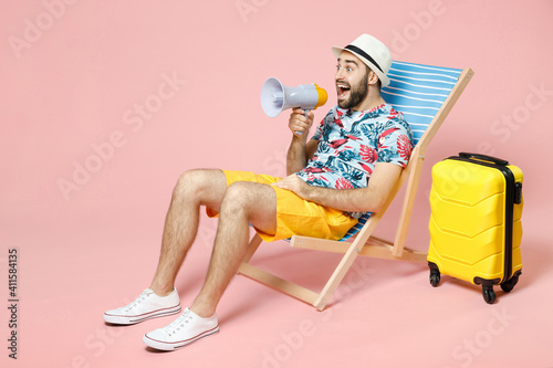 Fototapeta Full length shocked traveler tourist man in summer clothes hat sit on deck chair screaming in megaphone isolated on pink background. Passenger traveling on weekend getaway. Air flight journey concept. obraz na płótnie