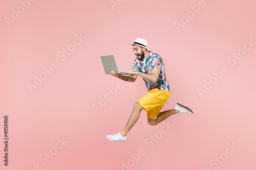 Full length side view of excited traveler tourist man in summer clothes hat jumping working on laptop computer isolated on pink background. Passenger traveling on weekend. Air flight journey concept.