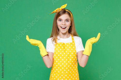Fotografie, Obraz Surprised little kid girl housewife 12-13 in yellow apron rubber gloves for cleaning spreading hands doing housework isolated on green color background children studio portrait