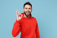 Young Caucasian Smiling Happy Bearded Attractive Handsome Positive Man 20s Wearing Casual Red Orange Hoodie Show Ok Okay Gesture Isolated On Blue Background Studio Portrait People Lifestyle Concept.
