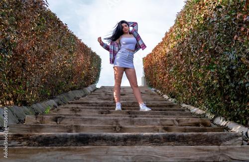 Fototapeta Mujer bella paseando al aire libre por un parque, desfile de moda