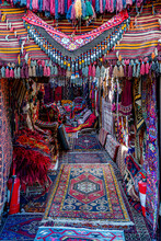 Turkish Bazaar Carpet Shop Entrance Decorated With Various Handmade Rugs With Colorful Tassels. Ornate Weaved Carpets. Ethnic Pattern Rugs. Traditional Asian Textures