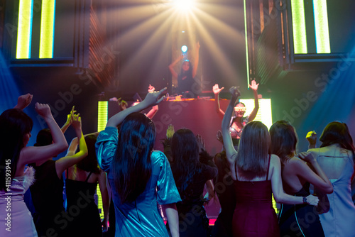 Group of people dance in disco night club to the beat of music from DJ on stage . New year night party and nightlife concept . © Blue Planet Studio