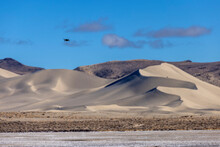 Tiny Black Drone Flies Towards Sand Dunes Of Sand Mountain OHV Park On A Clear Day With Blue Skies