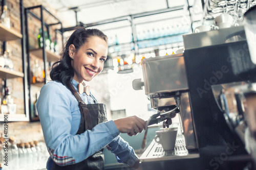 Fotografie, Obraz Beautiful barista makes espresso on a professional coffee maker in a cafe