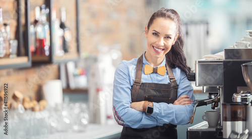 Fototapeta Happy waitress in an apron and wooden bow tie stands confidently next to a coffe