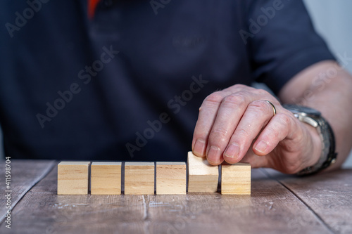 Fototapety, obrazy: blank template mock up of six timber block cubes , fifth cube pivoted with a man in the background holding the pivoted block