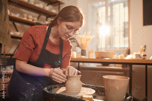 Canvas-taulu Warm toned portrait of young female artisan shaping clay on pottery wheel in sun