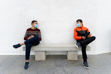 Stock Photo Of Teenagers Wearing Face Masks Due To Covid19 Using Tablet And Talking While Sitting In A Bench.