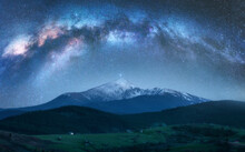 Arched Milky Way Over The Beautiful Mountains With Snow Covered Peak At Night In Summer. Colorful Landscape With Bright Starry Sky With Milky Way Arch, Snowy Rocks, Hills. Galaxy. Nature And Space