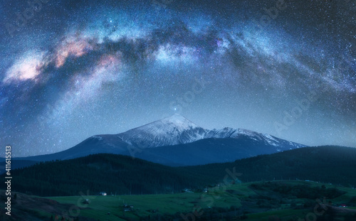 Obraz Arched Milky Way over the beautiful mountains with snow covered peak at night in summer. Colorful landscape with bright starry sky with Milky Way arch, snowy rocks, hills. Galaxy. Nature and space - fototapety do salonu