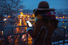 Woman Outside In City Park In Winter Using Phone Applications