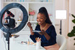 canvas print picture - happy young african american woman streaming a beauty vlog from home, online content creator applying a makeup on