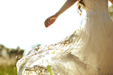 Midsection Of Bride In Dress Dancing Against Sky