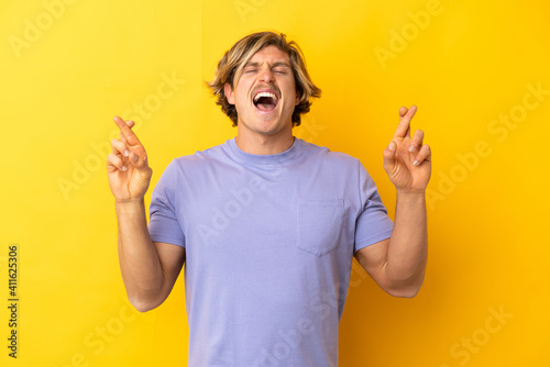 Fotografiet Handsome blonde man isolated on yellow background with fingers crossing