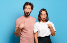 Young Couple Looking Shocked And Surprised With Mouth Wide Open, Pointing To Self