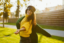 A Cheerful Girl In A Cap And Coat Whirls In The Park And Laughs At The Camera. Autumn. High Quality Photo