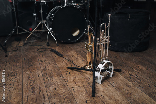 A black drum kit and a microphone stand are on stage and next to them are two trumpets (alto and bass) and a white tambourine Fototapeta