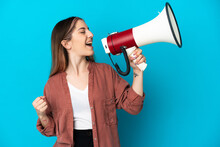 Young Caucasian Woman Isolated On Blue Background Shouting Through A Megaphone To Announce Something In Lateral Position