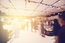 Defocused Image Of People In Illuminated Car Showroom