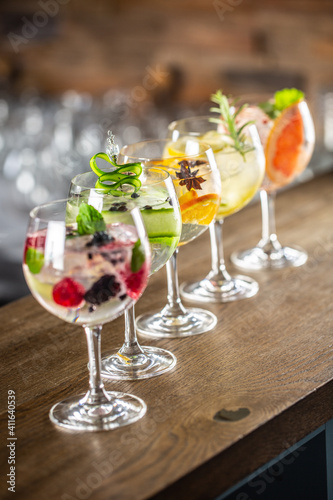 Gin tonic long drink as a classic cocktail in various forms with garnish in individual glasses such as orange, lemon, grapefruit, cucumber or berries © weyo
