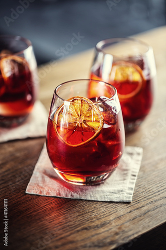 Negroni classic cocktail and gin short drink with sweet vermouth, red bitter liqueur and dried orange garnish © weyo
