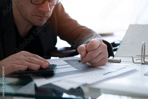 Businessman in glasses sign a document with bankruptcy lists. Application for declaration of consumer bankruptcy. © Daniel Jędzura