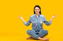 Keep Calm. Photo Of A Satisfied Calm Caucasian Young Woman With Closed Eyes, Meditates In Lotus Position On Isolated White Background