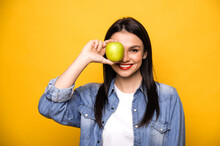 Happy Caucasian Woman Leads A Healthy Lifestyle. A Girl Stands On An Isolated Orange Background, Holds A Fresh Green Apple, Looks Into The Camera Covers One Eye With An Apple And Smiles. Healthy Food