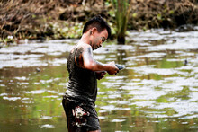 Side View Of Boy Covered In Mud Holding Turtle