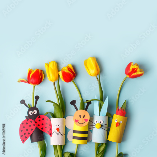 Obraz Happy easter spring toy collection and fresh flowers on blue background, kids holiday party concept background. Paper crafts, DIY. creative idea from toilet roll. reuse, recycle - fototapety do salonu