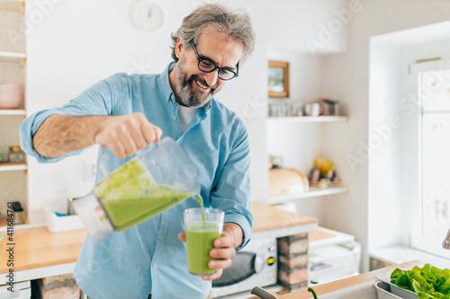 Papel de parede Senior man preparing smoothie in kitchen