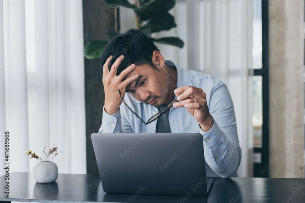 Fototapeta sad depression serious people from work,study stress concept.asian man feeling tired suffering using computer working work place.concept global economic,health problems