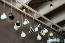 Coffee Or Tea Ceramic Mugs Dangling From Strings At A Cute Retro Cafe In The Wintertime.
