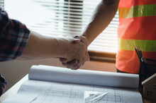 Midsection Of Architects Shaking Hands Over Blueprint On Table