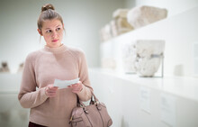 Young Woman With Guidebook Looking At Antique Sculptures In Museum
